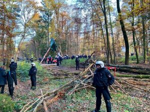 Cops stehen im Wald verteilt, im Hintergrund steht ein Tripod, unter dem besonders viele Cops stehen.